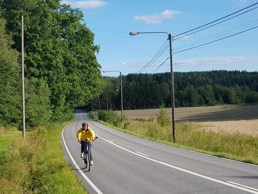 dam som cyklar längs landsväg