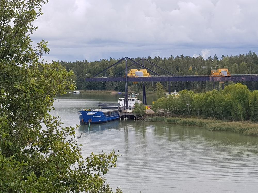 Lastfartyg vid stor kran, lövträd i förgrunden
