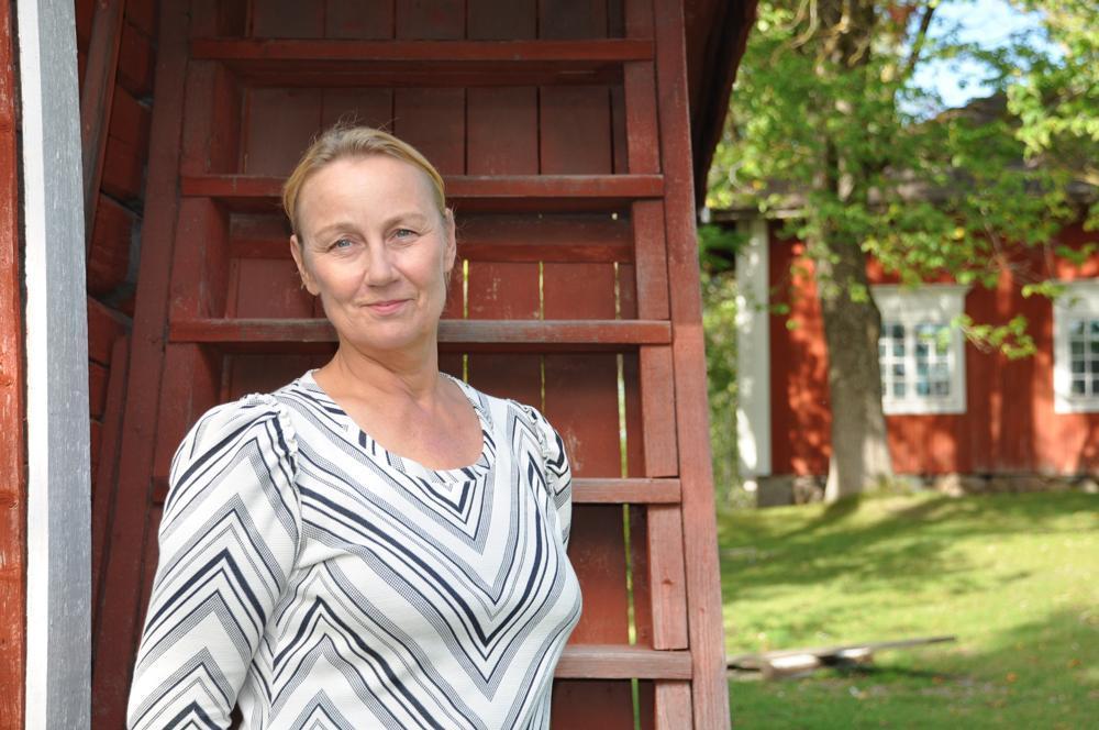 kvinna framför gammalt hus med trästege