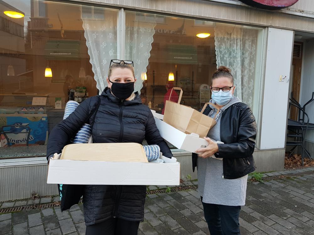 Två kvinnor med munskydd utanför stängt café
