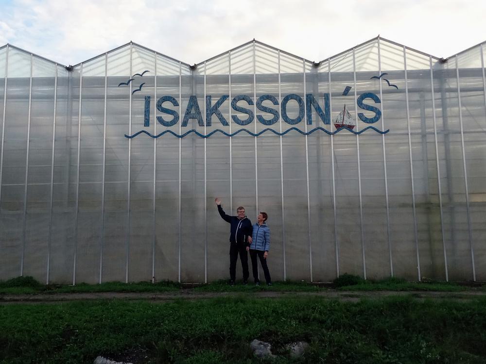 två odlare utanför ett stort växthus