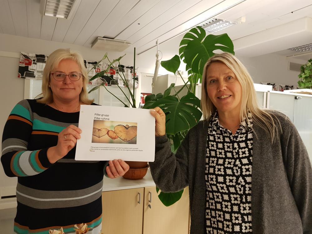 två kvinnor håller upp en broschyr