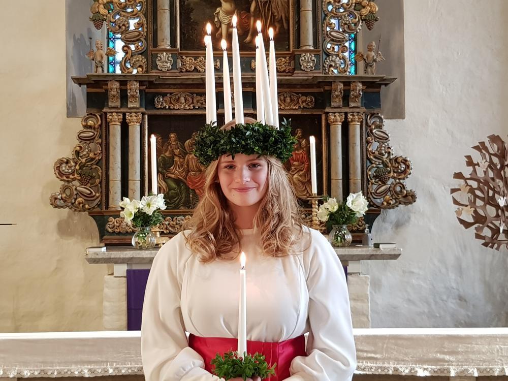 Lucia med tända ljus och ljus i handen