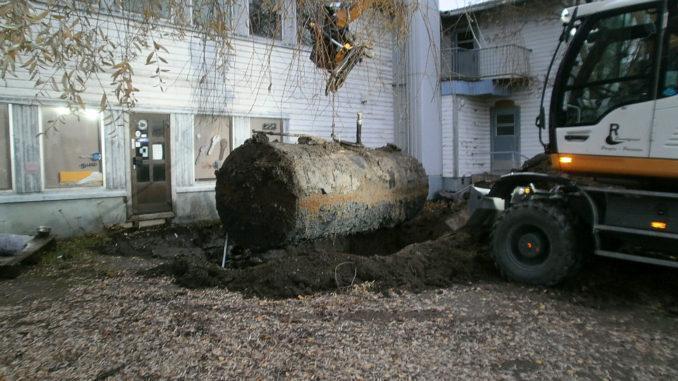 en gammal oljecistern lyfts upp ur marken