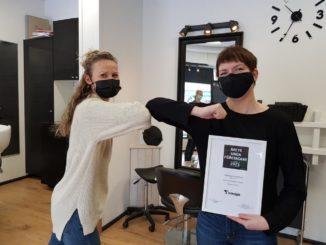 Två kvinnor med munskydd hälsar på varann med armbågarna