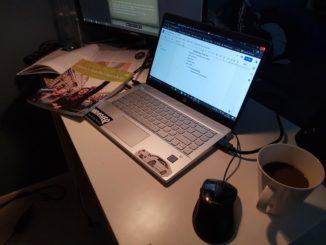 dator, skolböcker o kaffemugg i mörkt rum