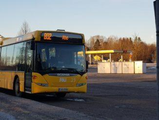 gul stadsbuss fotad i morgonljus