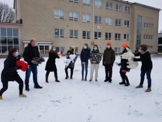 flera vuxna kring några ungdomar på en skolgård, vinter