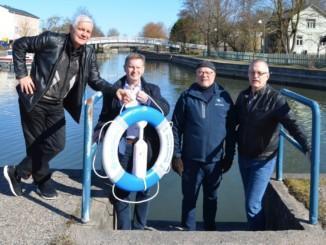 fyra män kring en blåvit livboj