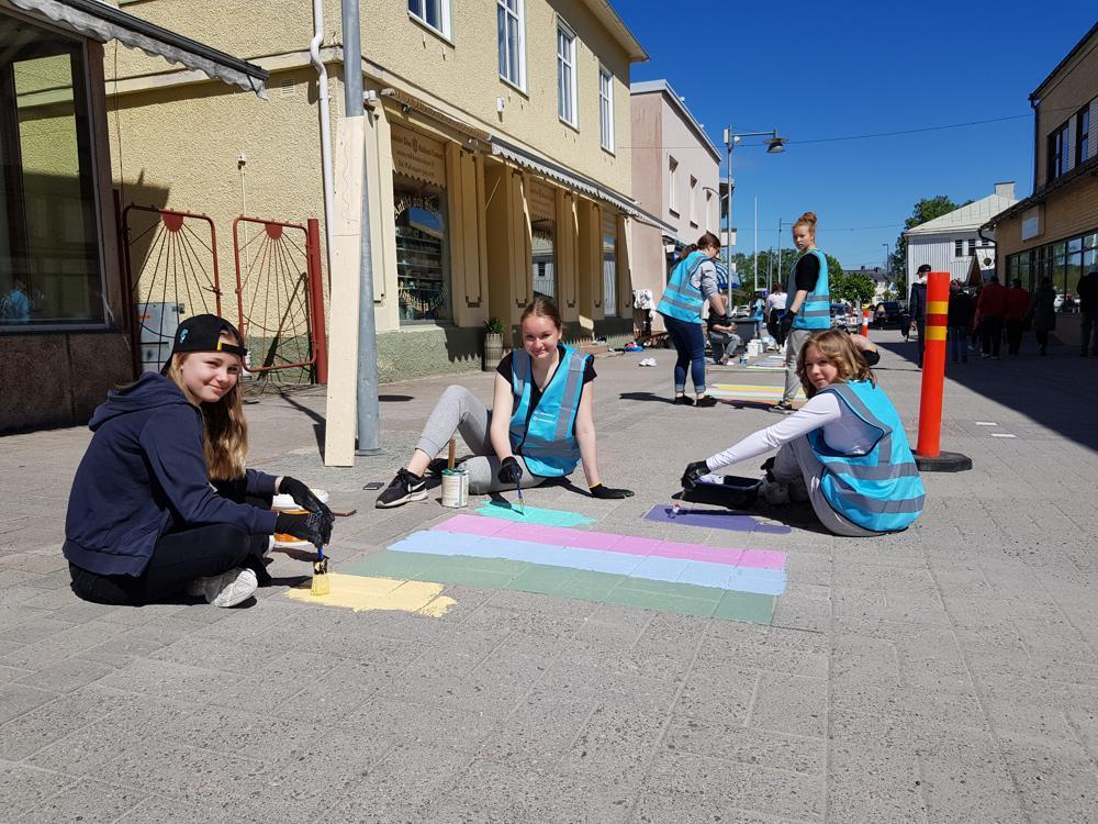 tre flickor målar ränder på gatan