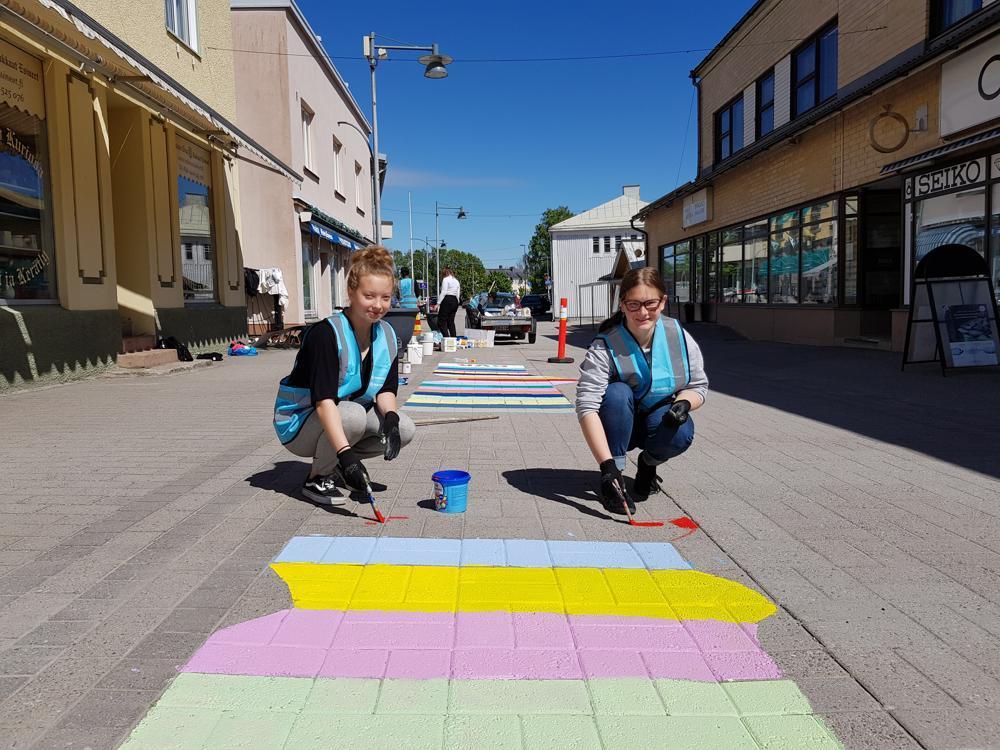 två flickor målar ränder på gatan