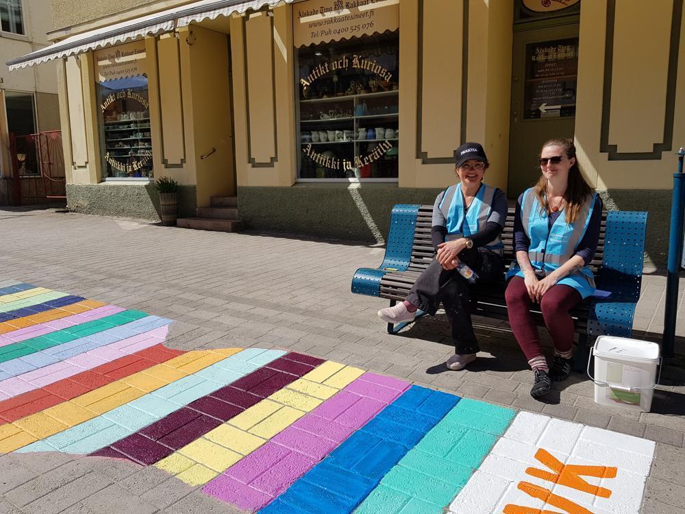 två kvinnor vid granna målade ränder på en gata