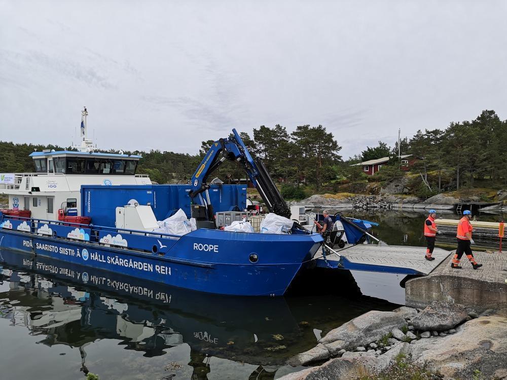 blått fartyg samlar in skrot i skärgården