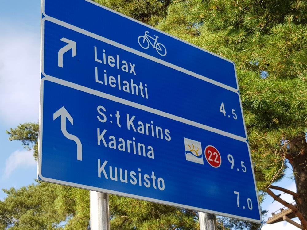 blå skylt med vit text för cyklister