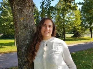 kvinna med långt hår vid ett träd