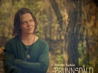 man med längre hår står med armarna i kors i trollskog