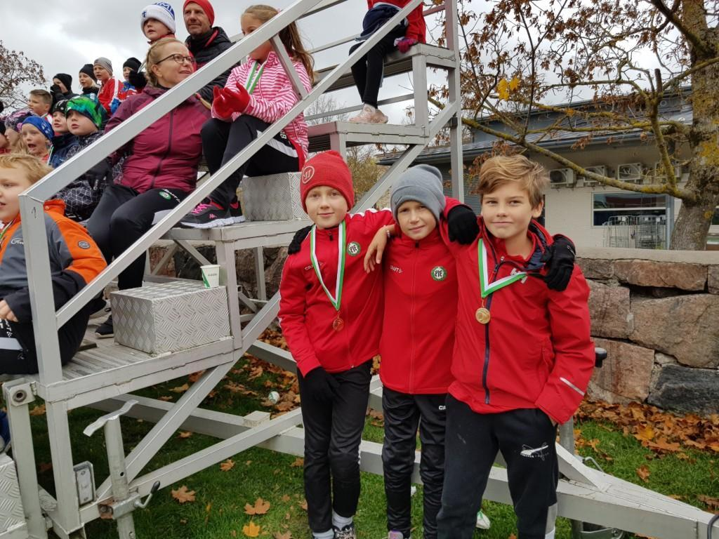 tre pojkar med röda sporttröjor och medaljer