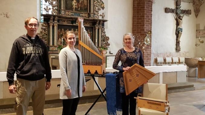 en man och två kvinnor vid altaret i en kyrka