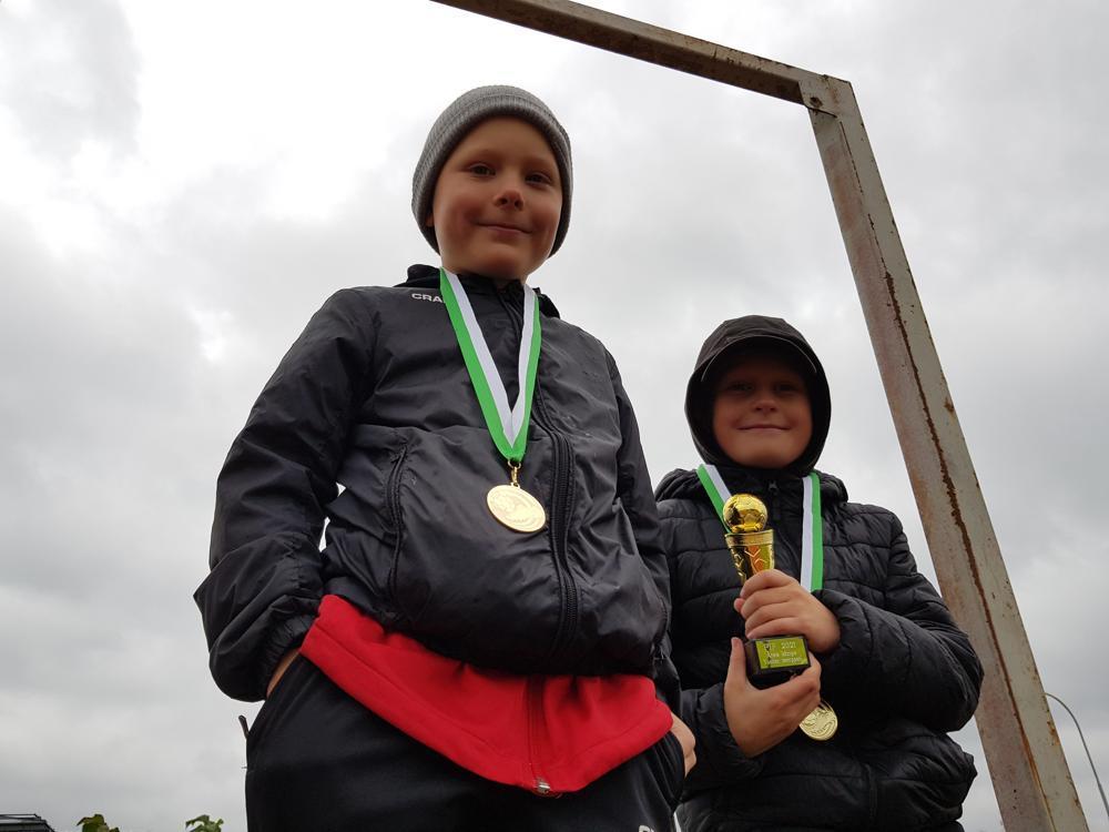 två fotisjuniorer med medaljer